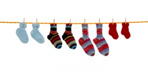 Four pairs of isolated handmade wool socks hanging on a rope.
